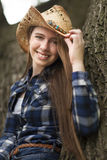 A teenage girl in a tree with a cowboy hat and plaid shirt. Stock Photography