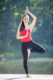 Teenage girl in tree yoga pose. Beautiful cheerful fit young woman in red tank top and black sporty leggings working out outdoors in park on summer day, standing Stock Images