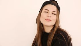 Teenage girl in trendy hip hop clothes and cap posing against white wall.  stock footage