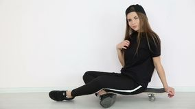 Teenage girl in trendy hip hop clothes and cap posing against white wall with skateboard.  stock video