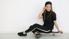 Teenage girl in trendy hip hop clothes and cap posing against white wall with skateboard.  stock footage