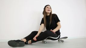 Teenage girl in trendy hip hop clothes and cap posing against white wall with skateboard.  stock video footage