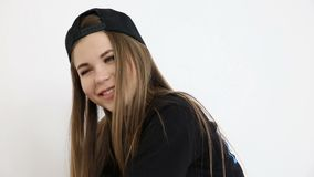 Teenage girl in trendy hip hop clothes and cap posing against white wall.  stock video