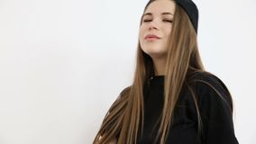 Teenage girl in trendy hip hop clothes and cap posing against white wall.  stock video footage