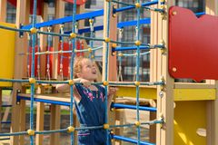 Teenage girl try to climbing on the rope wall. She is playing with the rope wall to develop motor activity at the playground stock photo