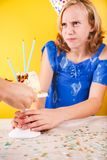 Teenage girl trying to keep birthday cake. One person party. Con. Cept of birthday party, messthetics and misconduct. Vertical Royalty Free Stock Image