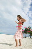 Teenage Girl Twirling Hula Hoop On Sandy Beach Royalty Free Stock Photo
