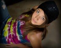 Teenage girl with tye-dyed shirt and skull cap. Young teenage girl looking at camera Royalty Free Stock Image