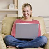 Teenage girl typing on laptop in chair Royalty Free Stock Photo