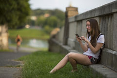 Teenage girl typing a message on smartphone, outdoors. Walking. Stock Image