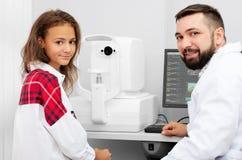 Teenage girl udergoes eye survey. Smiling teenage girl udergoes eye survey with doctor with modern diagnostics device in ophthalmologic clinic royalty free stock images