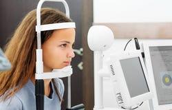 Teenage girl udergoes eye survey royalty free stock photo