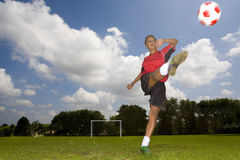 Teenage girl in uniform kicking soccer ball royalty free stock photography