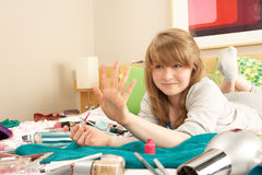 Teenage Girl In Untidy Bedroom Painting Nails Royalty Free Stock Photos