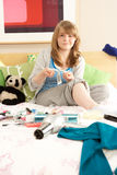 Teenage Girl In Untidy Bedroom Waxing Legs Stock Photo