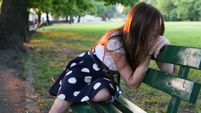 Teenage girl upset and crying sitting on a Park bench. Problems of teenagers. stock video