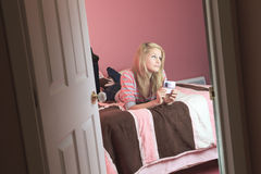 Teenage girl use cellphone in her room Stock Photo