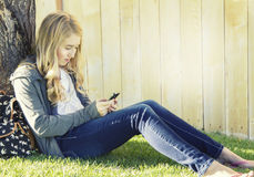 Teenage girl using a cell phone. Texting, surfing the internet or playing a game, in an outdoor setting Royalty Free Stock Photo