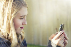 Teenage girl using a cell phone. Texting, surfing the internet or playing a game, in an outdoor setting Stock Photos