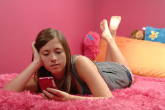 Teenage girl using cellphone. Teen girl uses her cellphone to text messages Royalty Free Stock Photography