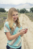 Teenage girl using cellphone walking down a country dirt road. Outdoors in a rural area Royalty Free Stock Photos