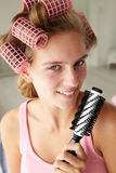Teenage girl using curlers in her hair Stock Photo