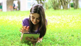 Teenage girl using digital tablet on grass stock footage