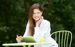 Teenage Girl Using Digital Tablet In Outdoor cafe Stock Photography
