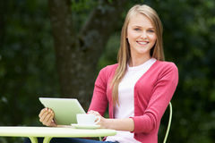 Teenage Girl Using Digital Tablet In Outdoor cafe Royalty Free Stock Photos