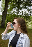 Teenage girl using inhaler portrait stock image