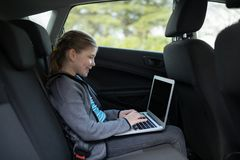 Teenage girl using laptop in the back seat Stock Photography