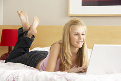Teenage Girl Using Laptop In Bedroom Stock Photography