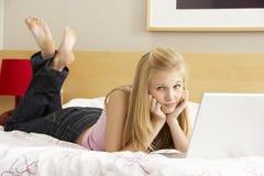 Teenage Girl Using Laptop In Bedroom. Looking at camera stock photos