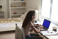 Teenage girl using laptop computer at a desk in her bedroom Royalty Free Stock Images