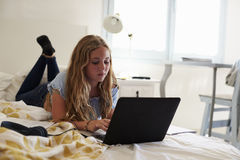 Teenage girl using laptop lying on her bed Royalty Free Stock Image