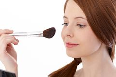 Teenage girl using makeup brush smiling Stock Photography