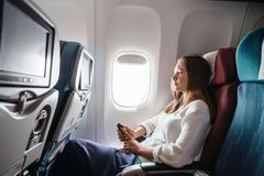 Teenage girl travelling by airplane royalty free stock photos