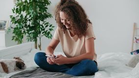 Teenage girl using mobile phone in her bedroom. Teenage girl using mobile phone on the bed in her room stock footage