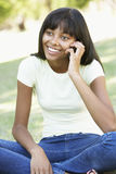 Teenage Girl Using Mobile Phone In Park Royalty Free Stock Photo