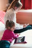 Teenage girl using mobile phone together with her little sister watching animated movie on tablet stock photos