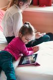 Teenage girl using mobile phone together with her little sister watching animated movie on tablet stock images