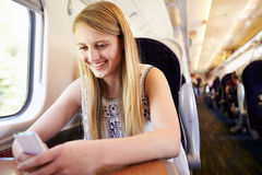 Teenage Girl Using Mobile Phone On Train Journey Royalty Free Stock Photos