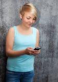 Teenage girl using smart phone Stock Images