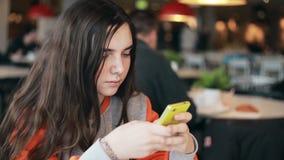Teenage girl using smartphone in cafe. stock video