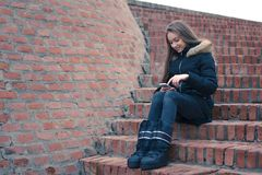 Teenage girl using smartphone sitting by brick wall. Teenage girl using smartphone outside smiling surfing messaging connecting communicate Stock Image