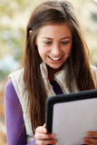 Teenage Girl Using Tablet Computer Outdoors stock photo