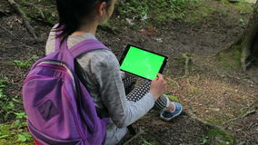 Teenage girl using tablet pc with green screen. Teenage girl searching on tablet pc with copy space sitting in the forest stock video