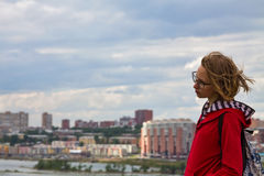 Teenage girl with view of city. Teenager girl standing with view of the city and cloudy sky Royalty Free Stock Photography
