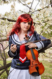 Teenage girl with a violin in the blooming garden stock image