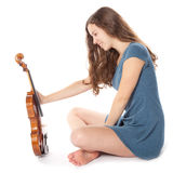 Teenage girl with violin sits in studio Royalty Free Stock Photography